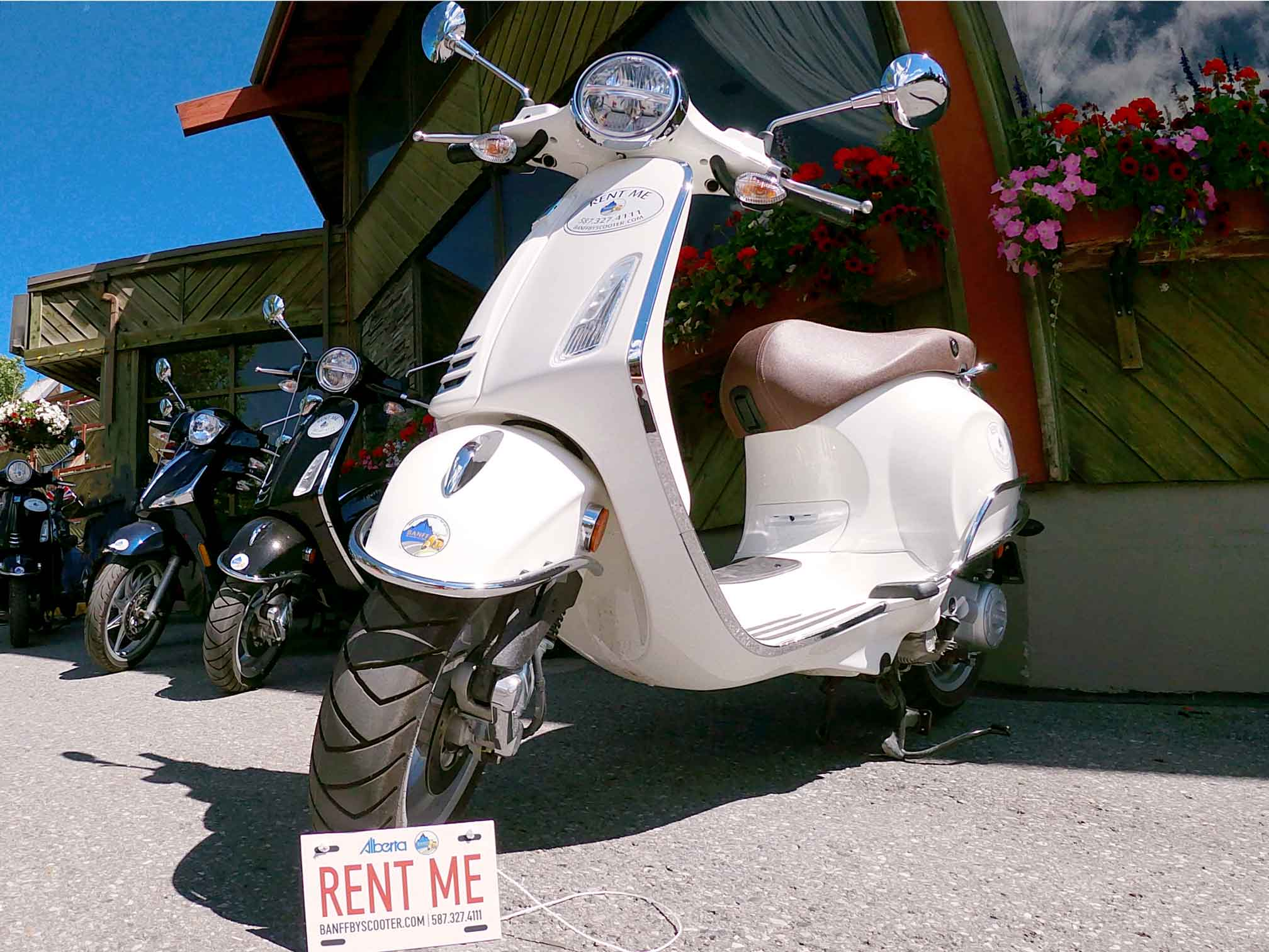 Scooters lined off with rent me sign at Banff By Scooter
