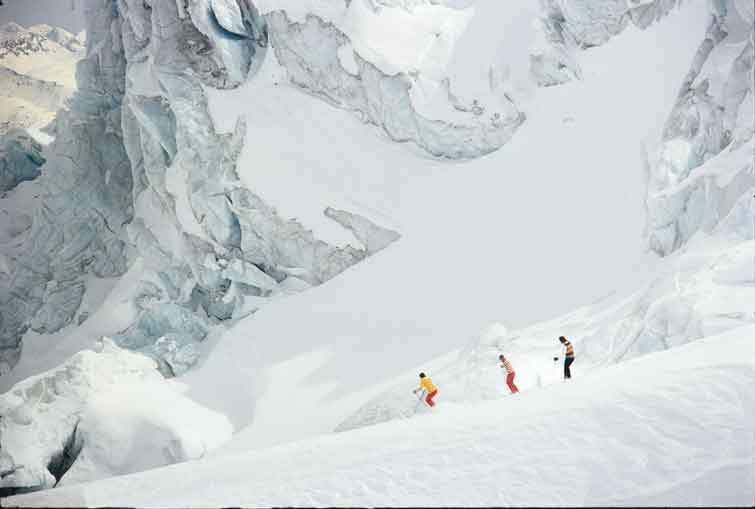Three skiers under a large glacier. Historical 1981 photo courtesy of CMH Heli-Skiing & Summer Adventures