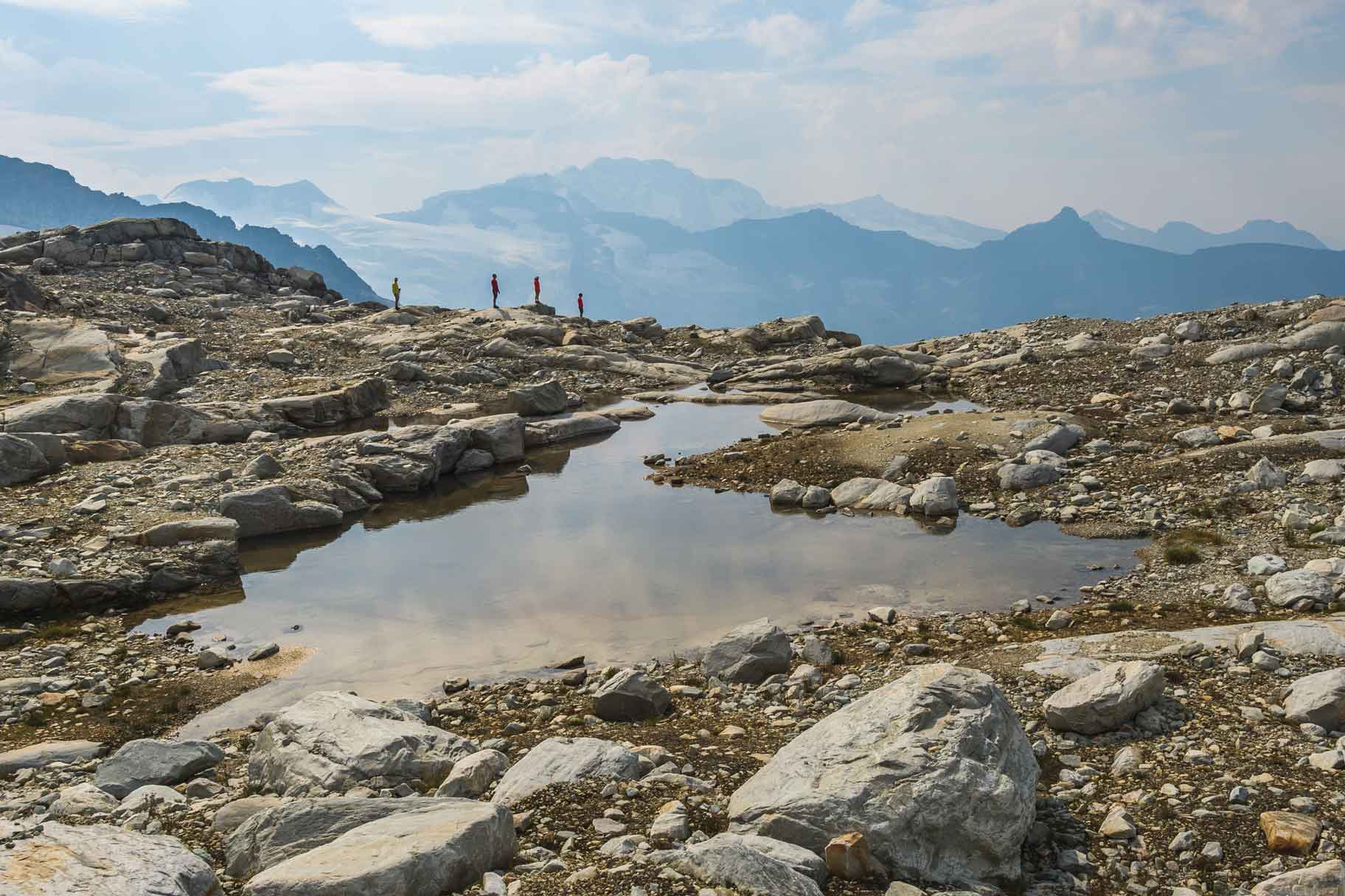 Four people walk off the beaten path at the edge of a small pond with mountain scenery in the background