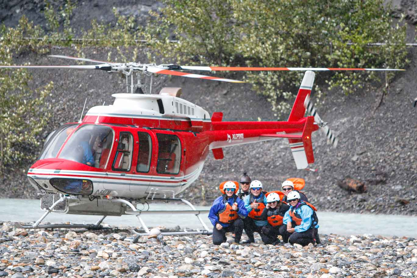 A group of rafters crouch near a helicopter, awaiting transport to the next section of river