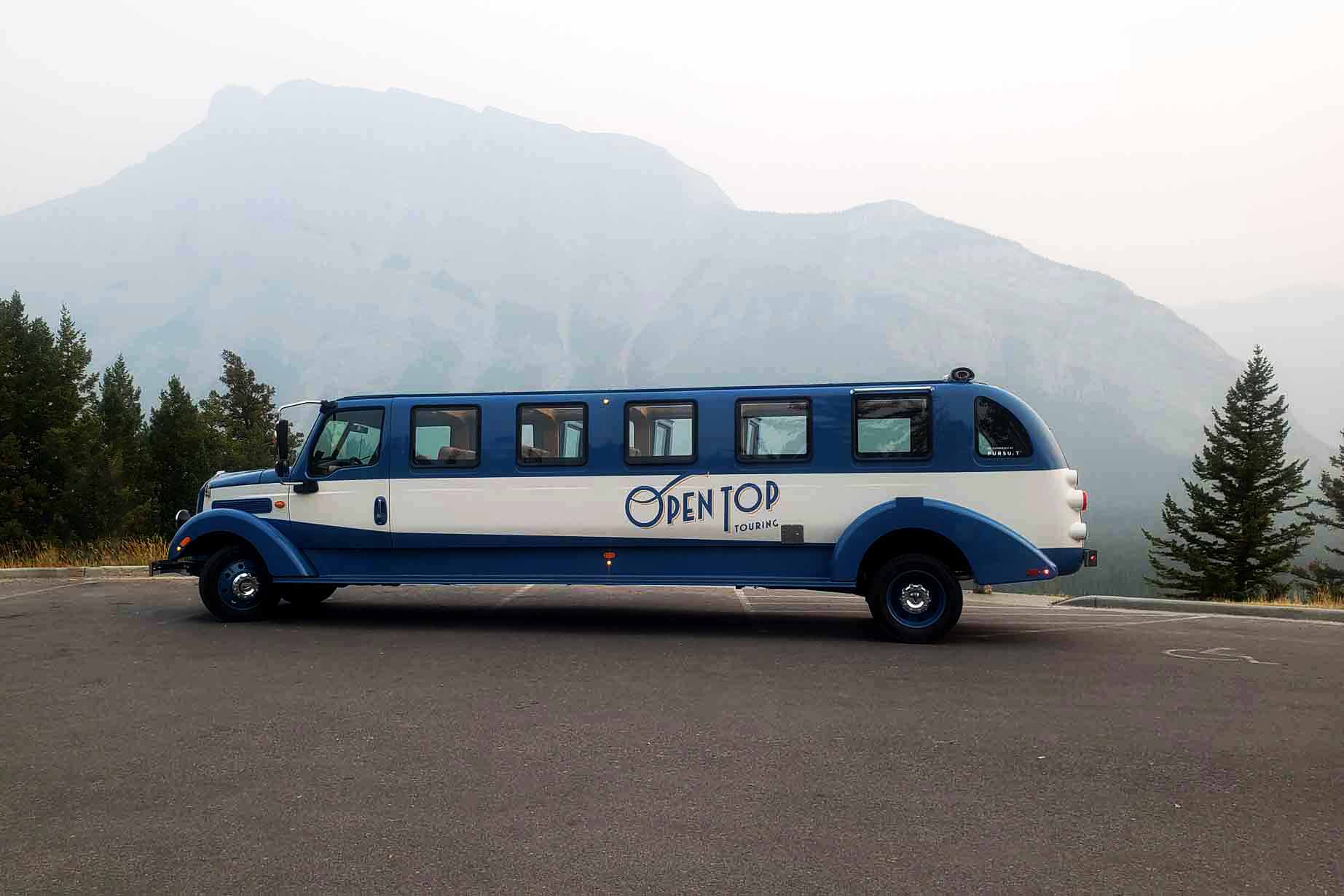 Open Top Touring bus in front of Mount Rundle at the Tunnel Mountain scenic lookout